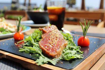 Foto tataki de atún rojo con soja y sésamo blanco sobre cama de rúcula aromatizada snack bar Maraú Beach Club